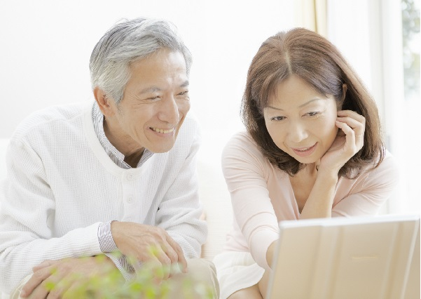 ノートパソコンを見るシニア夫婦