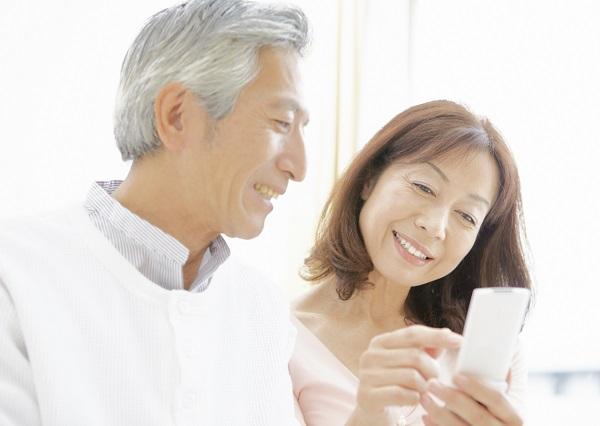 携帯電話を見るシニア夫婦